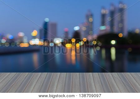 Opening wooden floor, Blurred light nigh view office building and water reflection