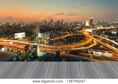 Opening wooden floor, blurred lights night view over highway intersection with city downtown background