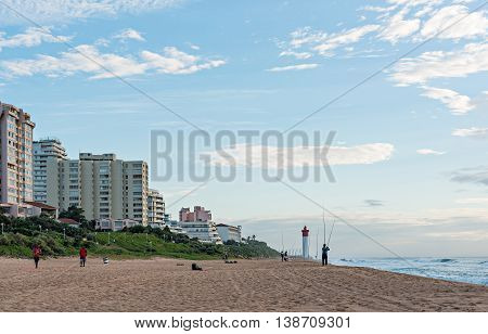 DURBAN SOUTH AFRICA - MARCH 12 2016: Anglers and Lifeguards on the Umhlanga Rocks beachfront with Millennium Pier and Lighthouse in the distance