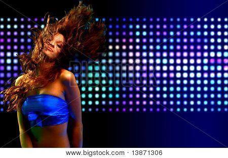 Schöne junge Frau, die in der Diskothek tanzen