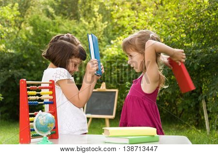 Two school girls quarrel and fight with books
