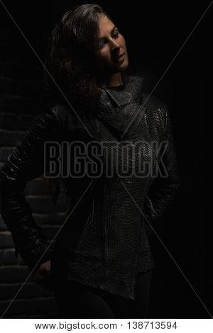 Fashion model posing in reptile leather vest near black brick wall.