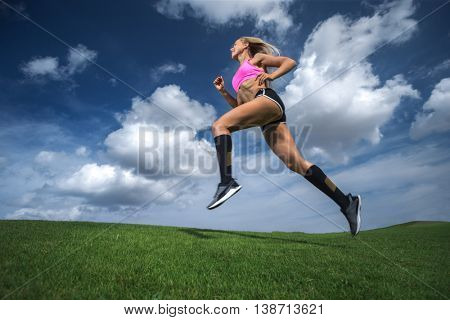 Female athlete training outdoor on green field.
