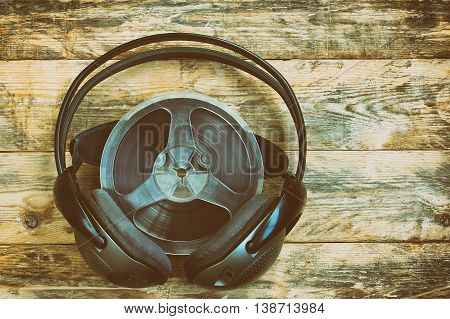 Music spool tapes and headphones on wooden table retro style toned effect