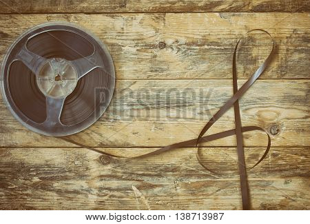 music record reel with tape shape treble clef on wooden table retro style toned effect