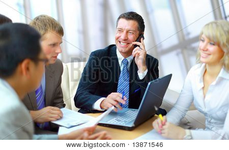 business man speaking on the phone while in a meeting