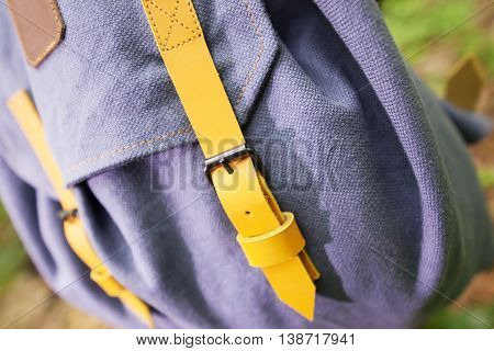 Traveler's handmade backpack on the tree photographed very close-up. Accessories buckle straps of backpack.