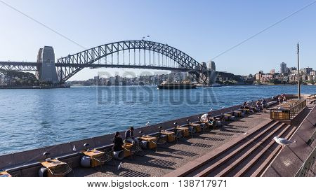Sydney - February 25 2016: The flags are developed over the Sydney Harbour Bridge and tourists relax on the waterfront near the Sydney Opera House February 25 2016 Sydney Australia