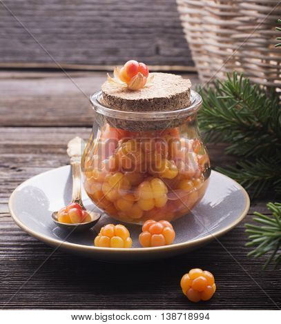 Juicy ripe cloudberry northern and sugar in a small glass jar on a wooden background