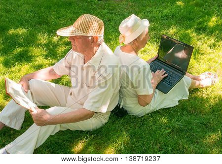 The happy old couple sitting on the green grass in park. The grandfather reading a book. The grandmother with a laptop