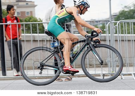 STOCKHOLM - JUL 02 2016: Side view of triathlete cyclist Emma Jackson (AUS) and audience in the Women's ITU World Triathlon series event July 02 2016 in Stockholm Sweden