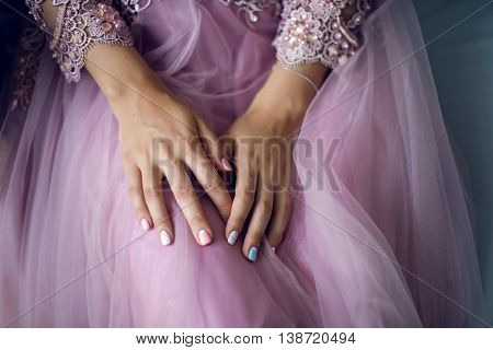 hands of a young girl lying on the pink lace dress