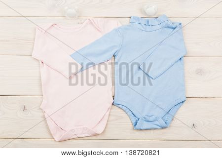 Two Onsies On Wooden Surface