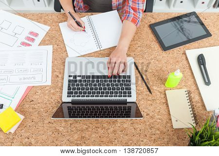 Woman working at office talbe. She is writing in her notebook and typing on laptop keyboard. Glue tablet and paper knife on cork table. Top view