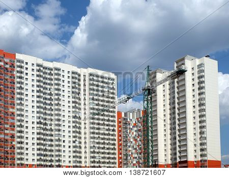 New high-rise modern apartment buildings construction in process ob bright sunny day front view horizontal with focus on construction tower crane