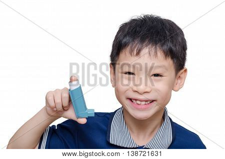 Asian boy holding inhaler and smiles over white
