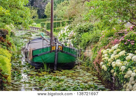 Historic restored ship in the narrow canal of the small Dutch village of Drimmelen. It's summer and many shrubs and plants are in full bloom.