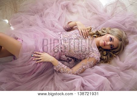 young sexy blonde girl in Lacy pink dress lying on the floor , opens his eyes and smiles