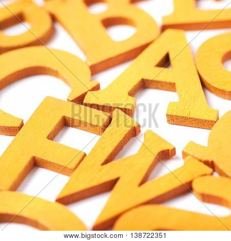 White surface covered with the multiple colorful orange painted wooden letters as a backdrop composition
