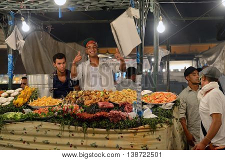 MARRAKESH - JULY 10: Unidentified people sells food in Jemaa el Fna Square at sunset, July 10, 2013 in a Marrakesh, Morocco. The square is part of the UNESCO World Heritage