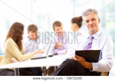 Portrait of a senior business man attending a conference with the rest of his business team