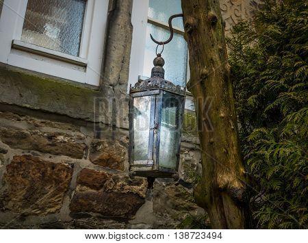 lantern on wooden pillar and stone wall