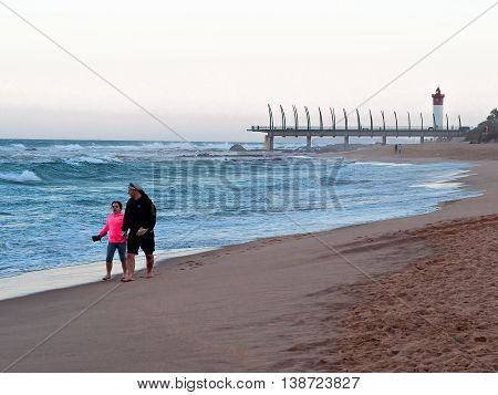 DURBAN SOUTH AFRICA - JULY 11 2016: People on the beach at Umhlanga Rocks with the Millennium Pier and lighthouse in the background.