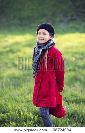girl in red raincoat and checkered scarf on green spring meadow