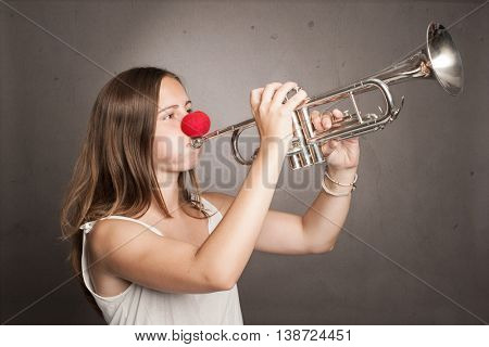 woman with red nose playing trumpet on a gray background