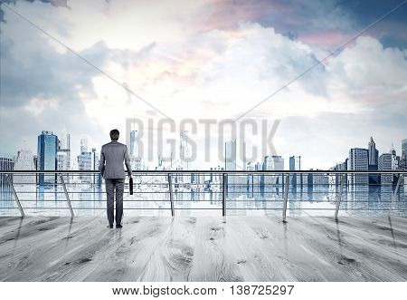 Businessman in gray suit looking at city thinking about something standing at balcony