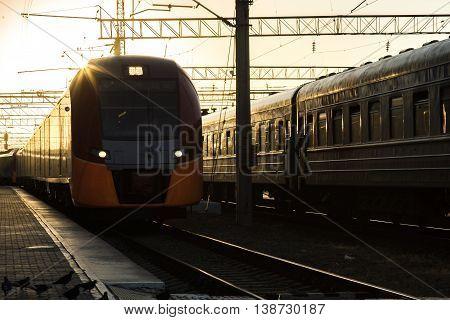 Railway Tracks a Major Train Station at Sunrise. Locomotive pulling wagons