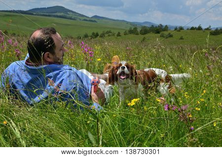 Man is resting on a spring field with his dog Cavalier King Charles Spaniel