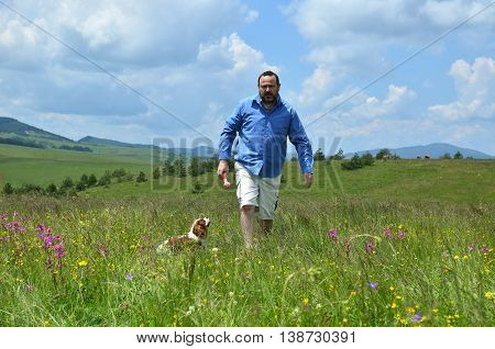 Man is playing on spring meadow with his dog Cavalier King Charles Spaniel