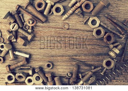 Photo of nuts bolts and screws on a shabby wooden background. Retro toned