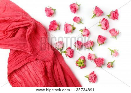 Assorted roses heads ans scarf. Various soft roses and scarf scattered on a white background, overhead view. Flat lay