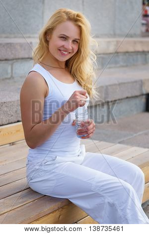 Caucasian blonde woman with bottle of water sits on banch outdoors