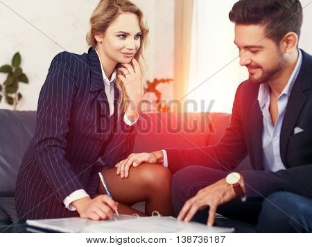 Businessman seduce businesswoman on sofa put hand on leg sexual harassment reviewing documents