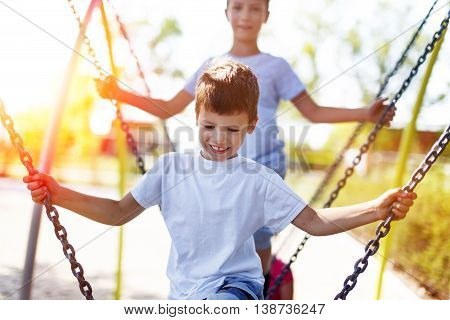 Little boys climbing on jungle gym outdoor in sunset