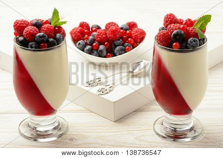 Delicious dessert - panna cotta with berry jelly and berries.