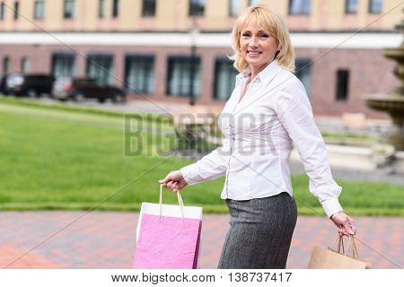 Blond mature woman enjoying shopping in town. She is standing with packages and posing. Woman is smiling happily