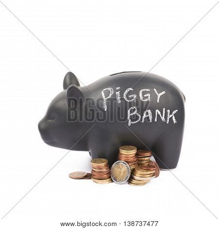 Words Piggy bank written with chalk on a black ceramic coin container next to a pile of euro coins, composition isolated over the white background