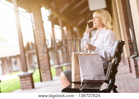 Happy mature woman having rest after shopping. She is sitting on bench with many packets. Woman is talking on mobile phone and smiling