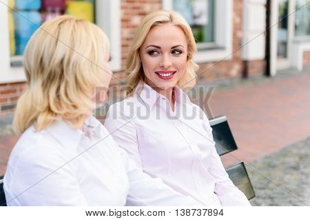 Cheerful mother and daughter are communicating and smiling. They are sitting on bench in city