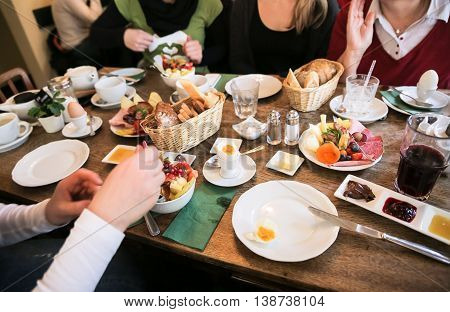 Young Happy Family Having Breakfast with tasty ingredients
