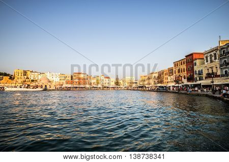 CHANIA, CRETE - JUNE 26, 2016: View of the old venetian port of Chania on Crete island Greece. Tourists relaxing on promenade.