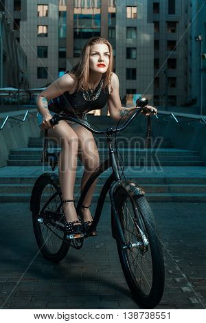 Girl in a rock style rides a bicycle through the city at night.