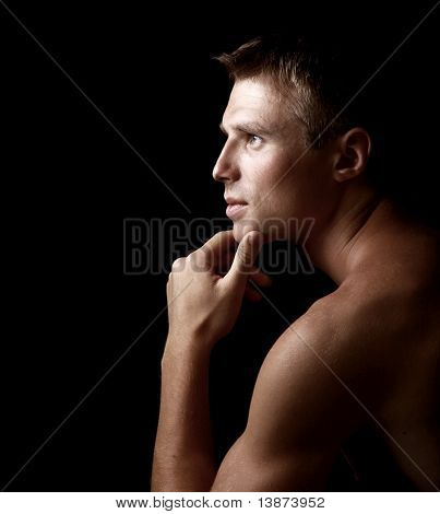 Shadowy dark close-up portrait of young good looking male model