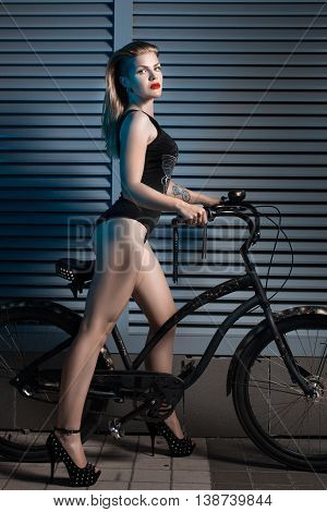Woman night outdoors holding a cruiser bicycle.