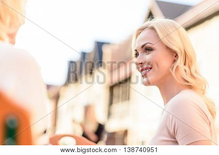 Happy young woman is spending time with her mother. She is looking at mature woman and smiling. They are sitting and talking outdoors