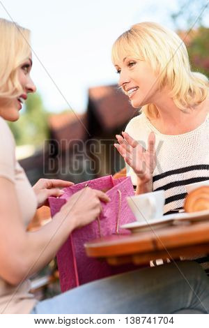 Young woman is sharing news with her mother. She is showing shopping packet and smiling. Ladies are sitting at table in cafeteria